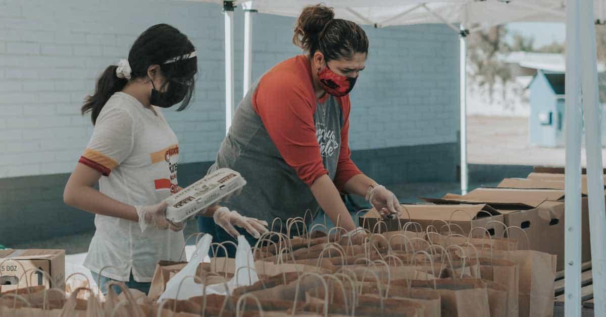 Two women volunteering by packing brown bags of food