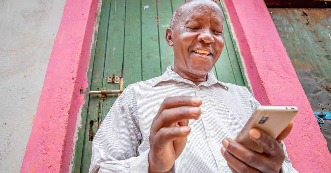 A Kenyan farmer in a white shirt poses for a photo with his mobile phone