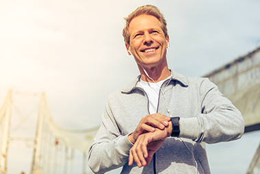 Man smiling and using smart watch