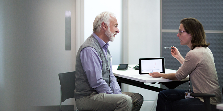 Man having discussion with woman in front of tablet