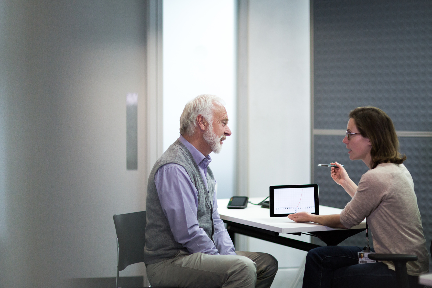 Man and woman discussing healthcare date in front of tablet