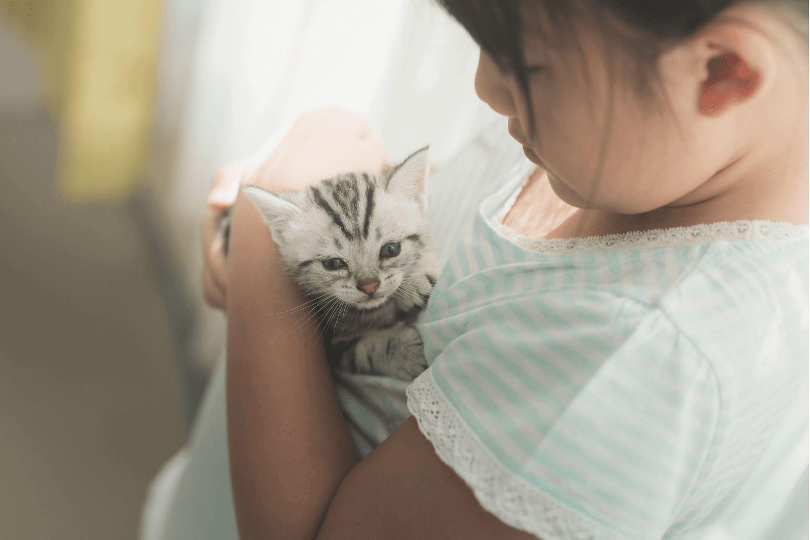 a girl hugging her cat