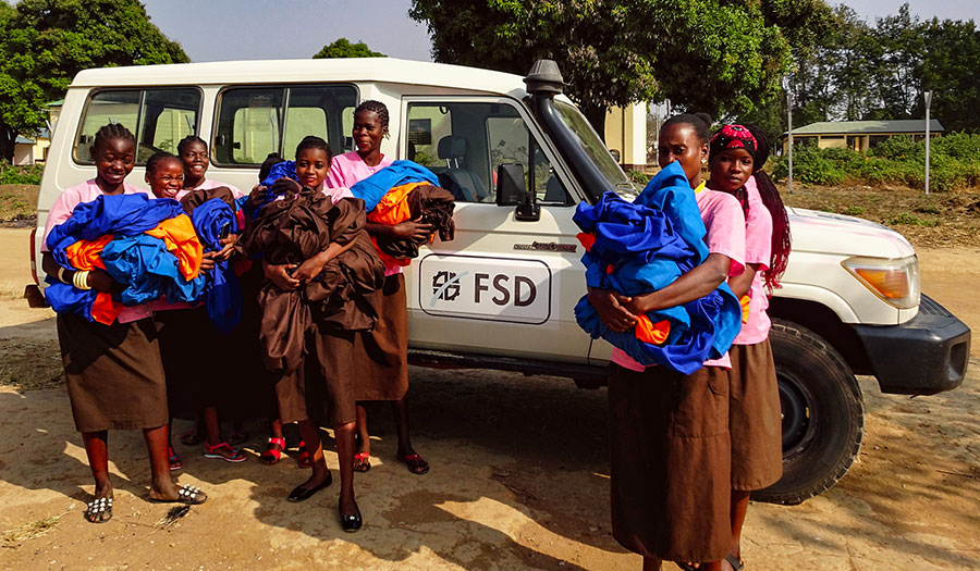 Women carrying material in front of a FSD vehicle