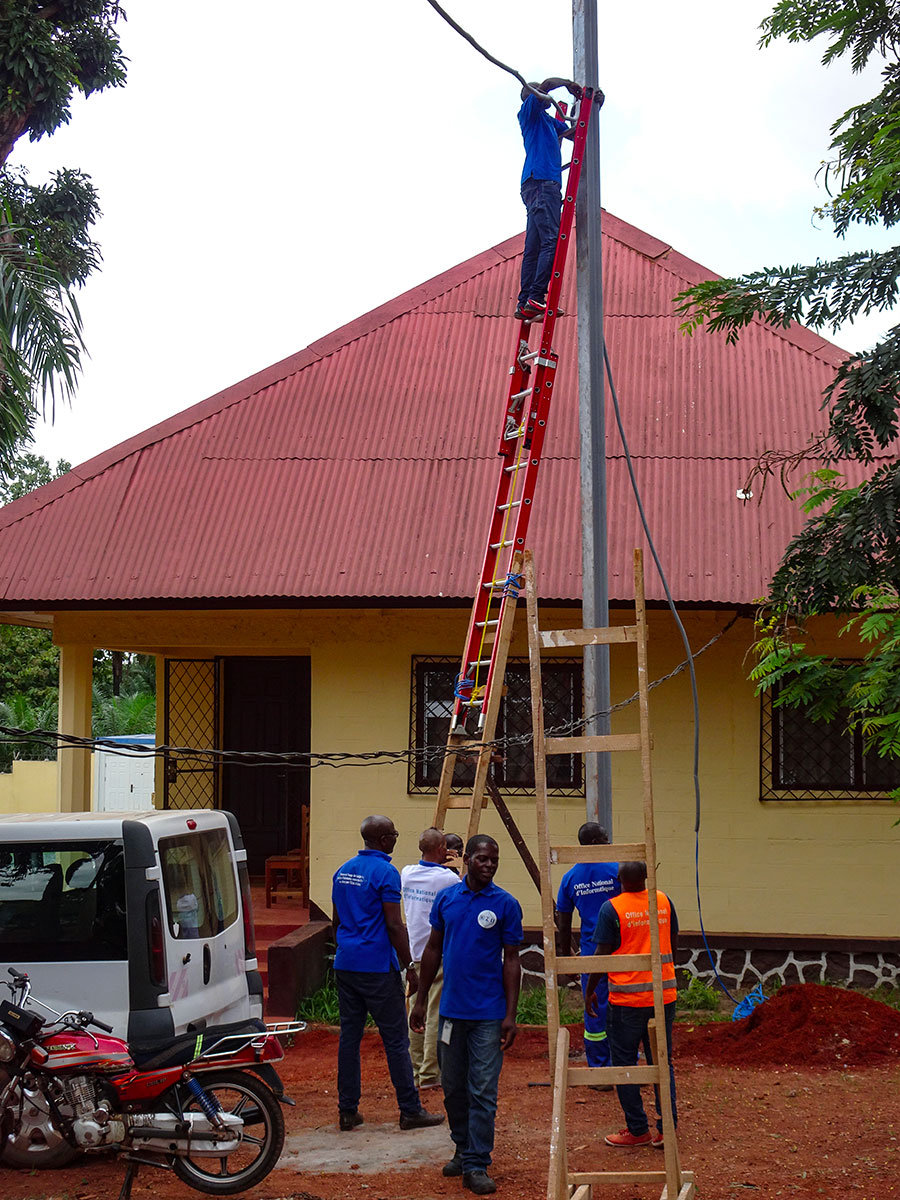 7 men (one on a ladder) working on the installation of streetlight