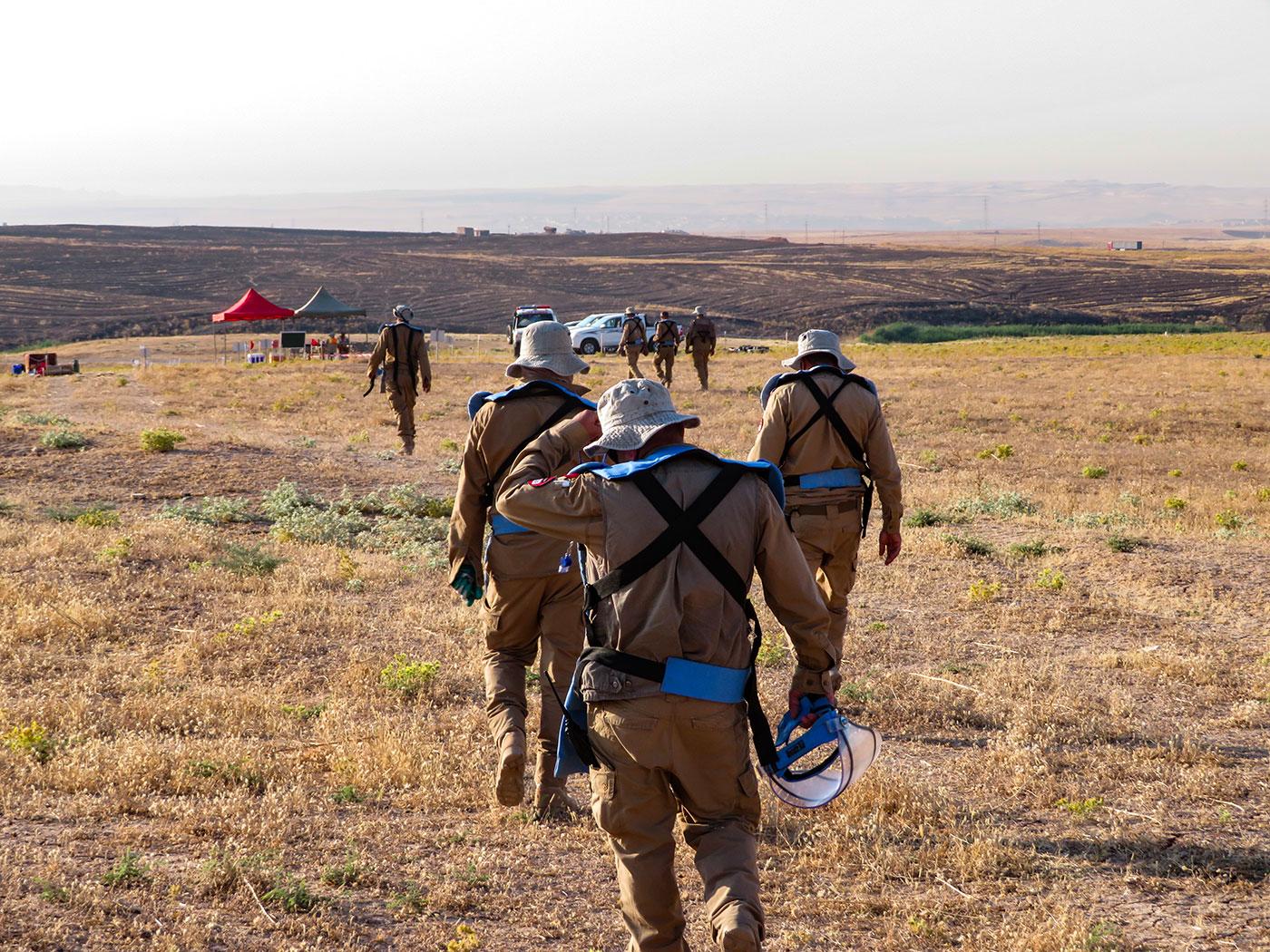 Des employés de la FSD marchant sur un terrain