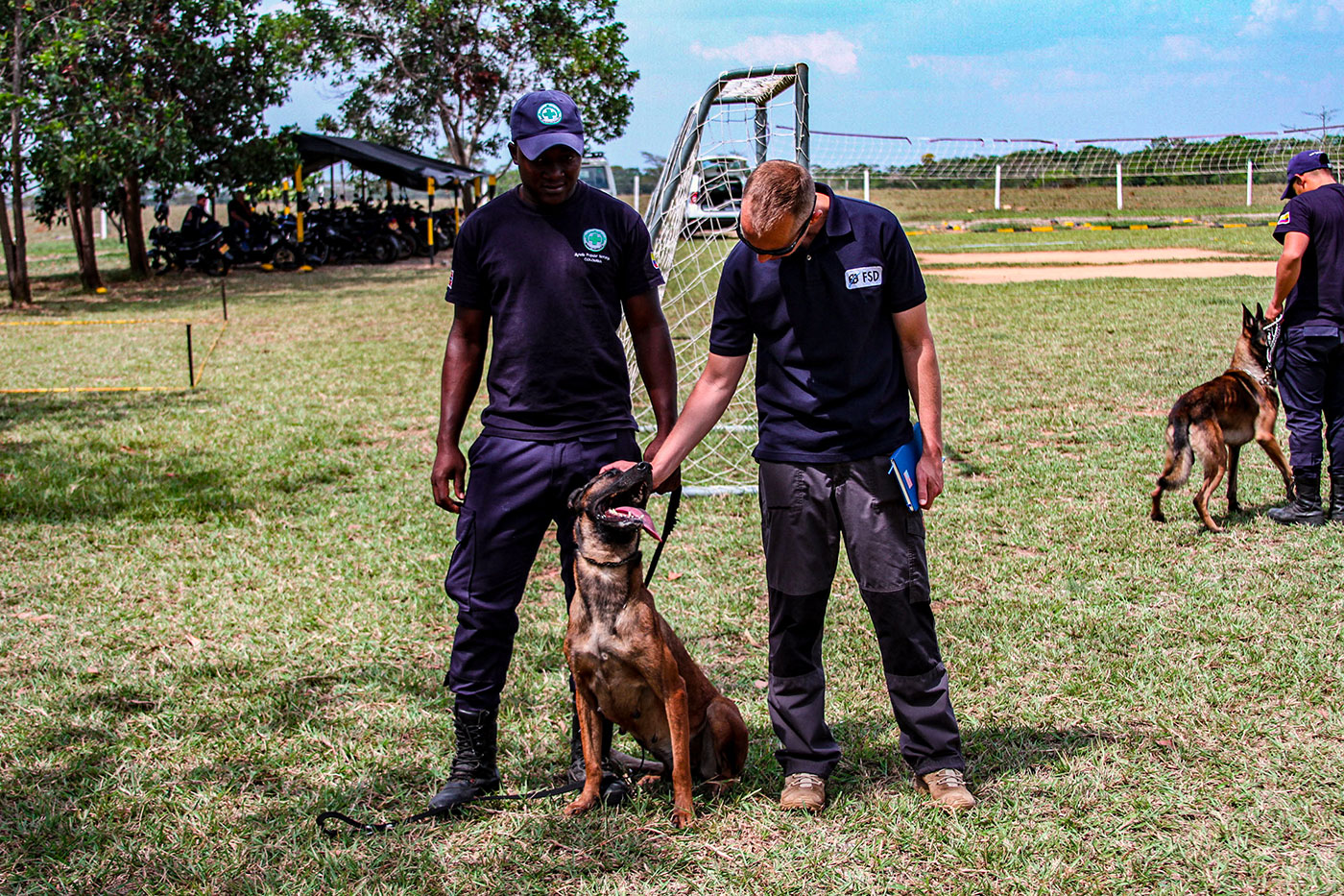 two fsd employees and a mine detection dog