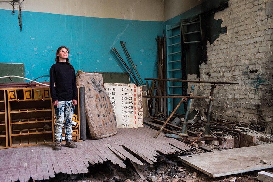 jeune fille dans un bâtiment endommagé