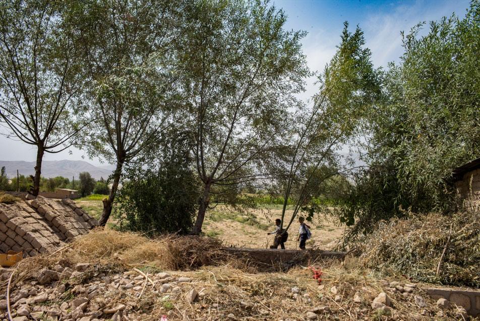landscape in tajikistan, two boys in the back