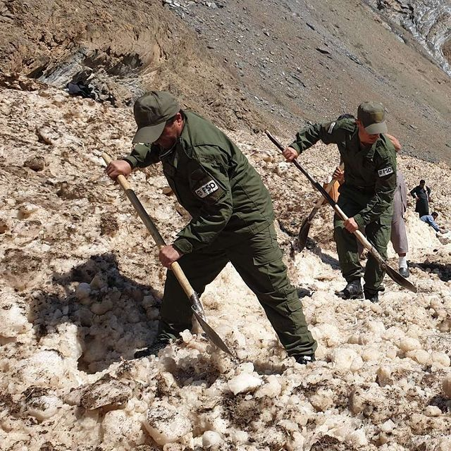 L'équipe FSD creuse pour enlever la neige de la route.