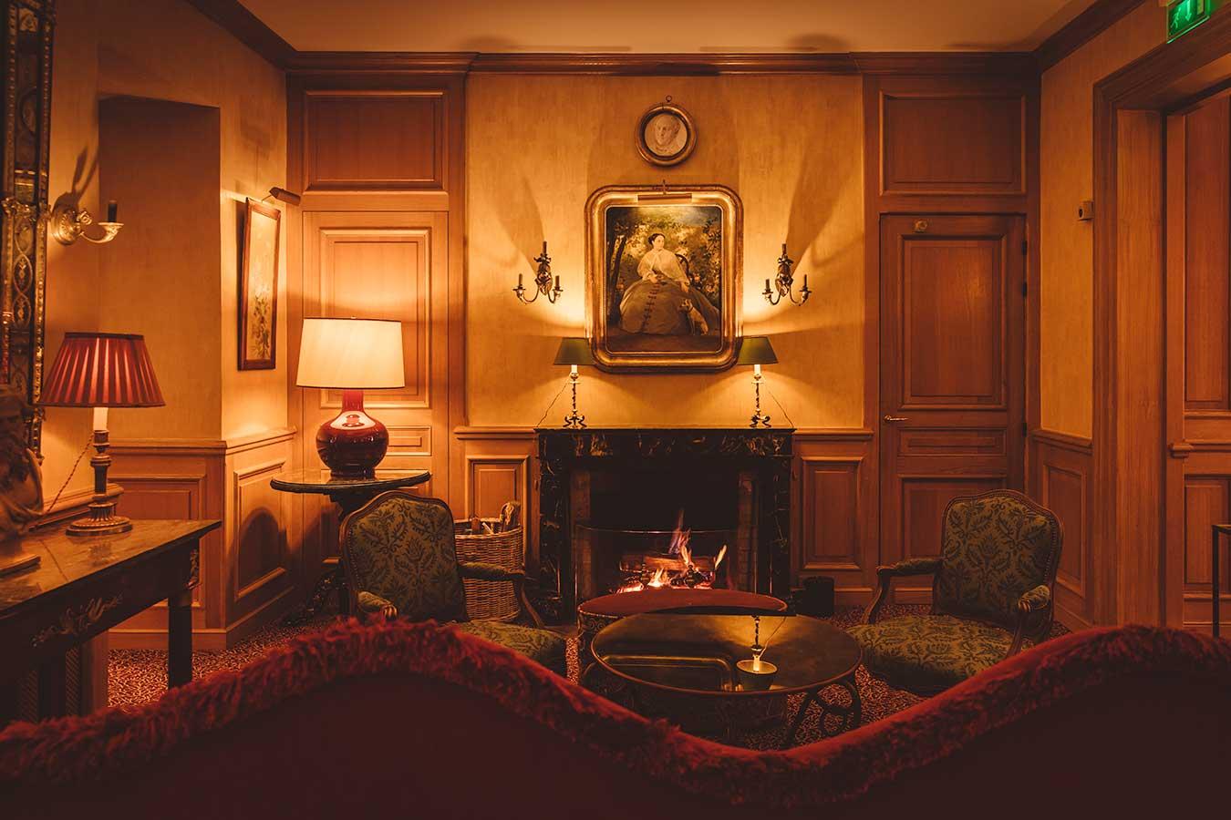Salon - Grand canapé rouge, table basse ronde avec verre de vin, deux fauteuils à motif vert, feu de cheminée et tableau