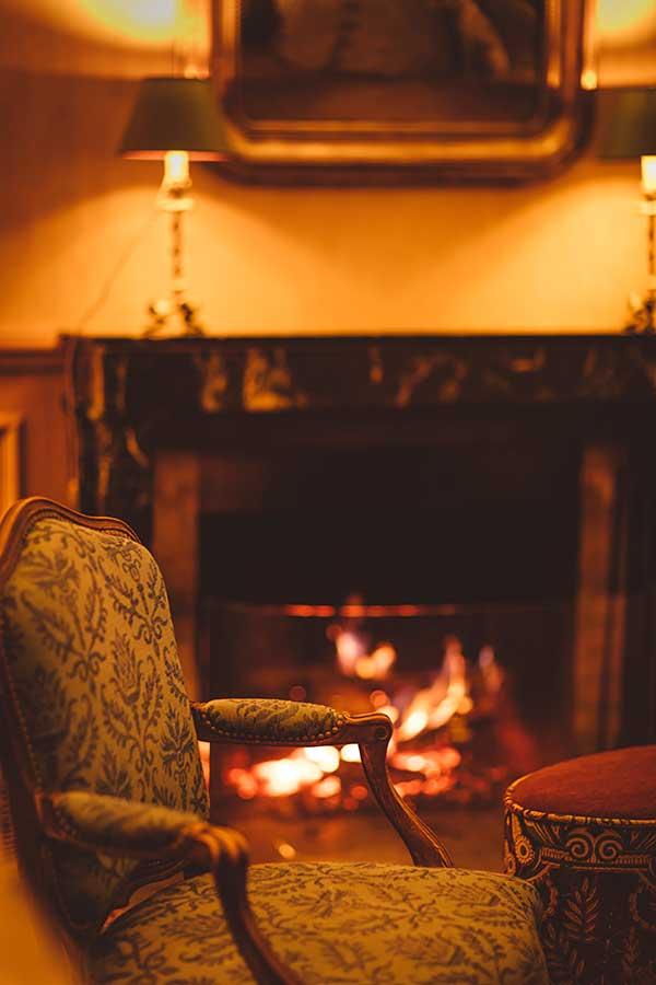 Salon - Fauteuil à motif vert, cheminée et feu de cheminée