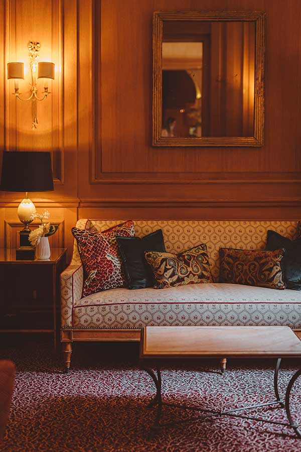 Salon - Grand canapé avec coussins, table basse en marbre, moquette à motif dans une harmonie de bleu, beige et rouge