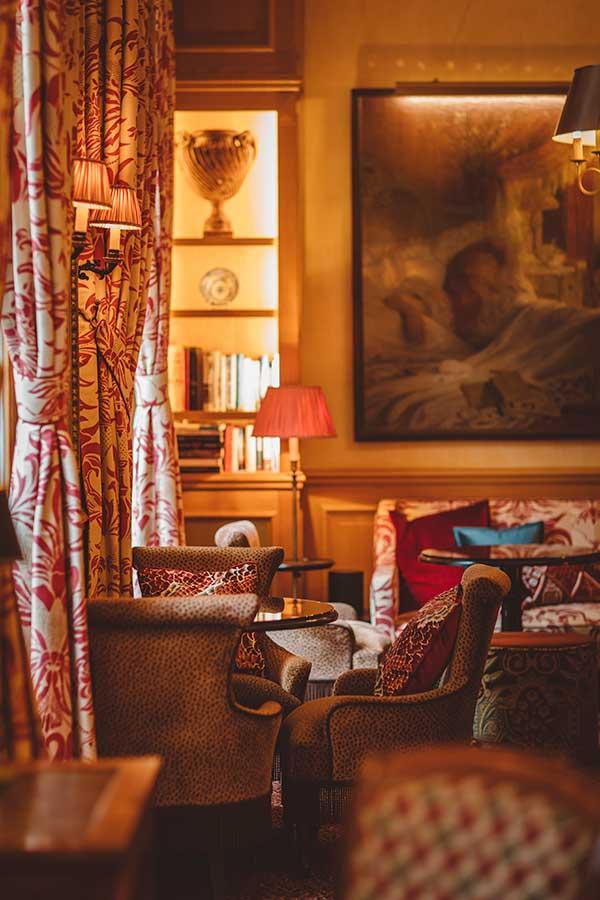 Salon -Bibliothèque, lampe, canapés et coussins en velours dans une harmonie de rouge