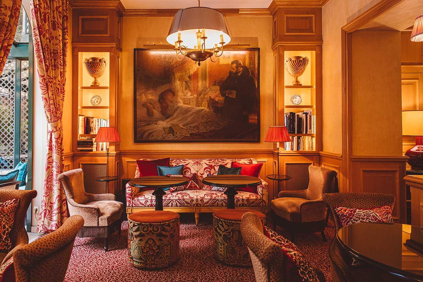 Salon - Fauteuils, canapés et tables rondes, grand tableau et bibliothèques attenantes, lumière venant de la verrière, dans une harmonie de beige et rouge