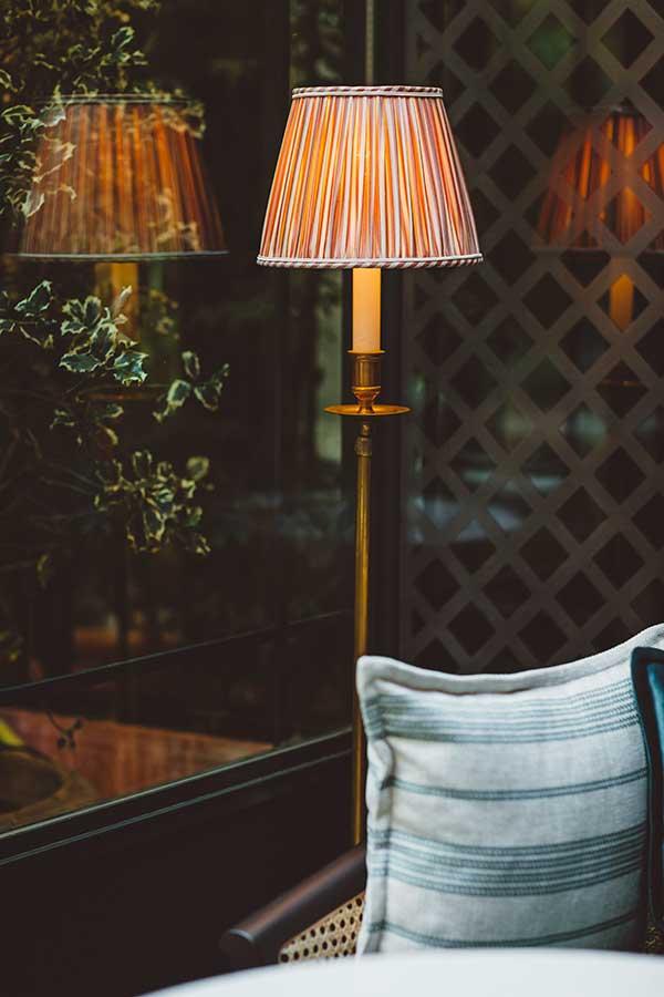 Salon - Lampe et coussin dans une harmonie de vert et blanc, sous la verrière donnant sur le jardin