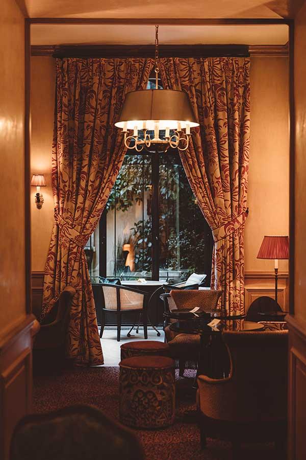 Salon - Encadrement du salon à la véranda, rideaux dans une harmonie de beige et rouge, donnant sur la verrière et le jardin