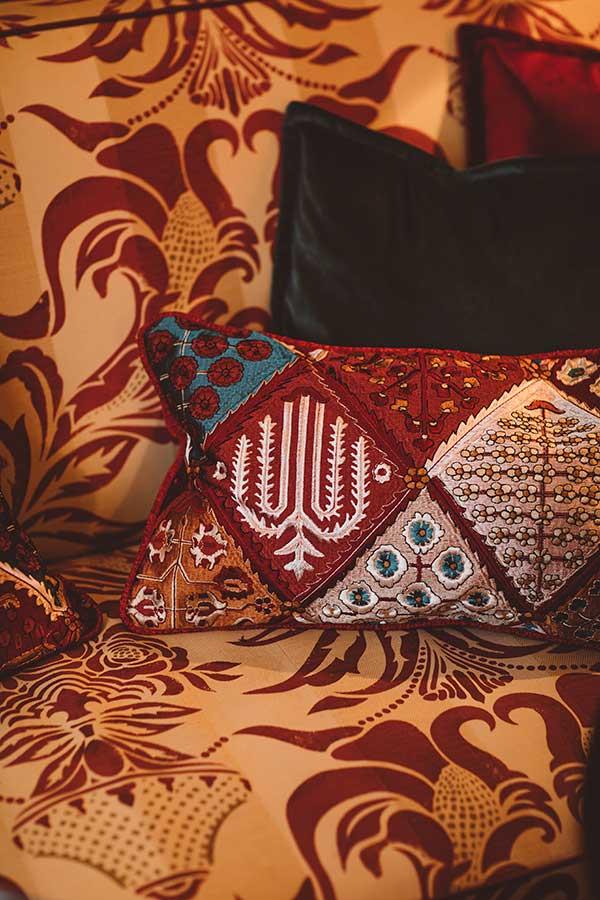 salon - Canapé beige à motif rouge, coussins en velours bleu et rouge bordeaux