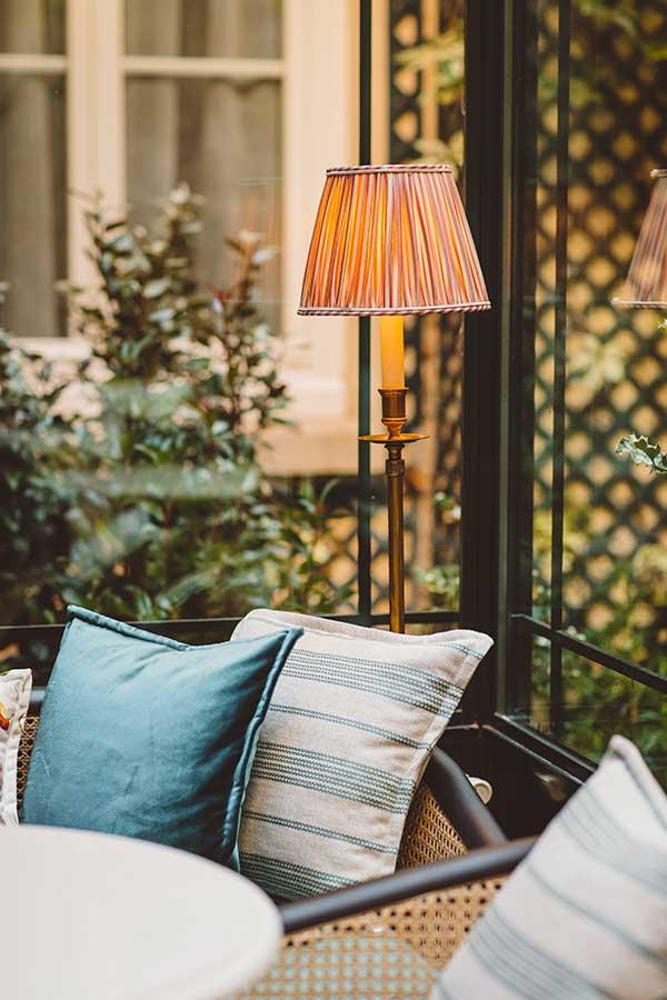 Salon - Beaux coussins vert et blanc, table ronde en marbre, lampe sous une verrière ensoleillée donnant sur le jardin