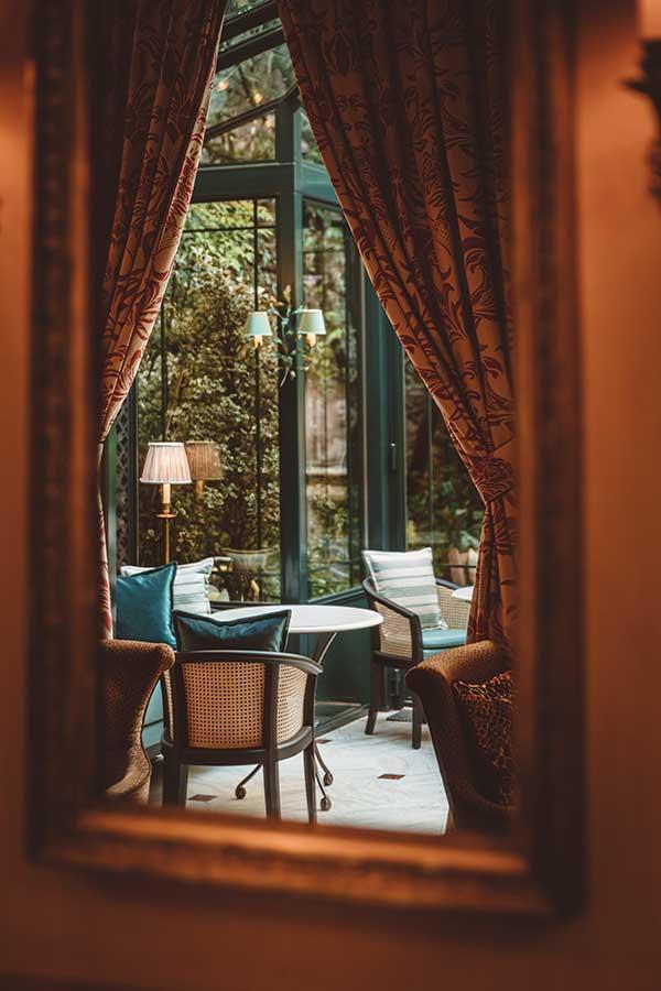 Salon - Dans un reflet de miroir, tables ronde en marbre, fauteuils et canapés dans une harmonie de vert et blanc, sous une verrière ensoleillée donnant sur le jardin