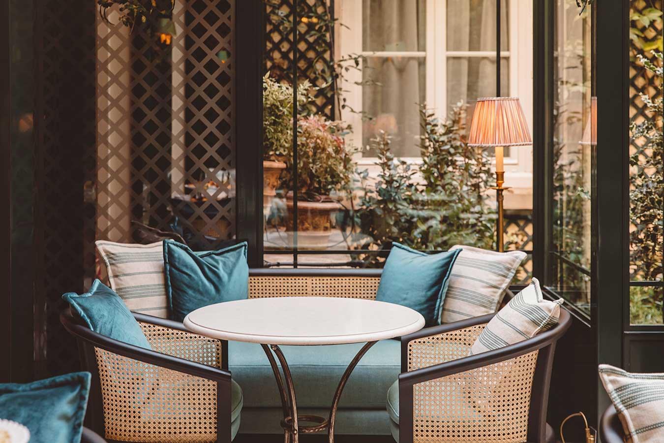 Salon - Table ronde en marbre, canapé avec coussins, fauteuils sous une verrière ensoleillée donnant sur le jardin, dans une harmonie de vert, noir et blanc
