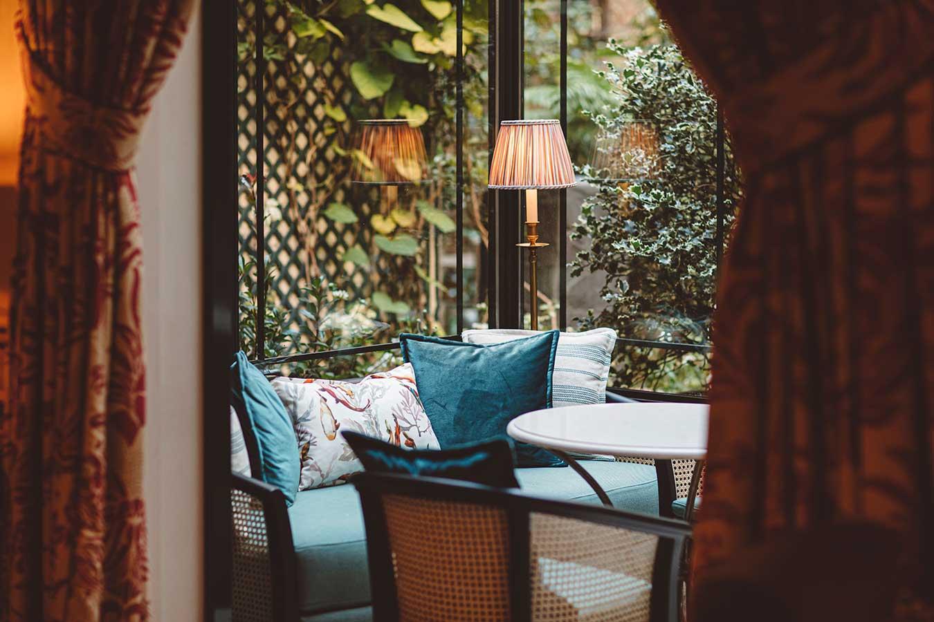 Salon - Table ronde en marbre, canapé avec coussins, fauteuil sous une verrière ensoleillée donnant sur le jardin dans une harmonie de vert, noir et blanc
