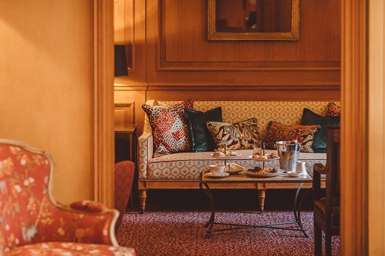 Tea time - Présentoirs à gâteaux sucré et salé, sceau à champagne disposés sur une table basse en marbre, canapés et coussins dans une harmonie de bleu, rouge et rose
