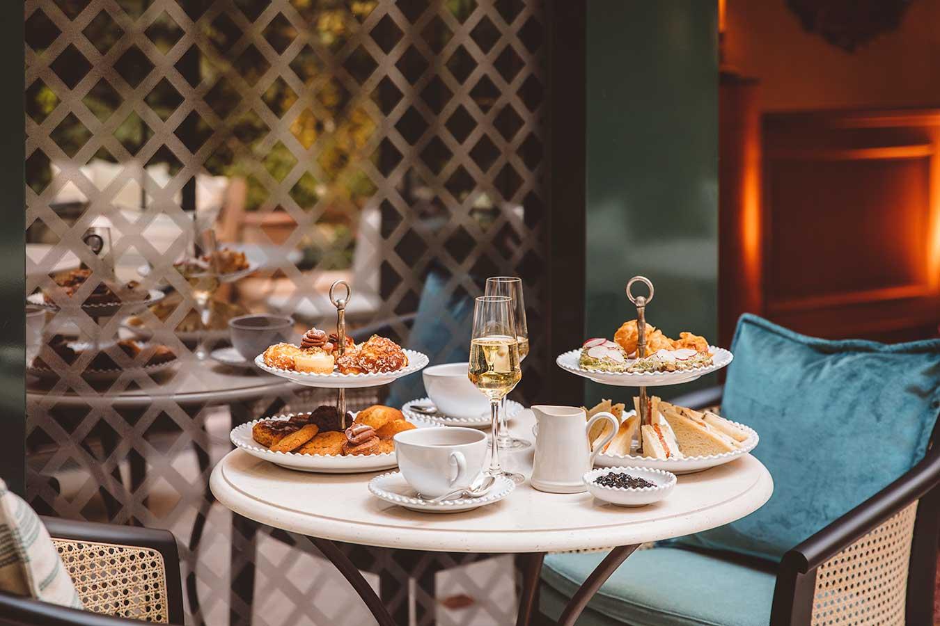 Tea time - Thé, présentoir à gâteaux sucré et salé, confiture, coupes à champagne disposés sur une table en marbre ronde, fauteuils, sous la verrière du Salon ensoleillée