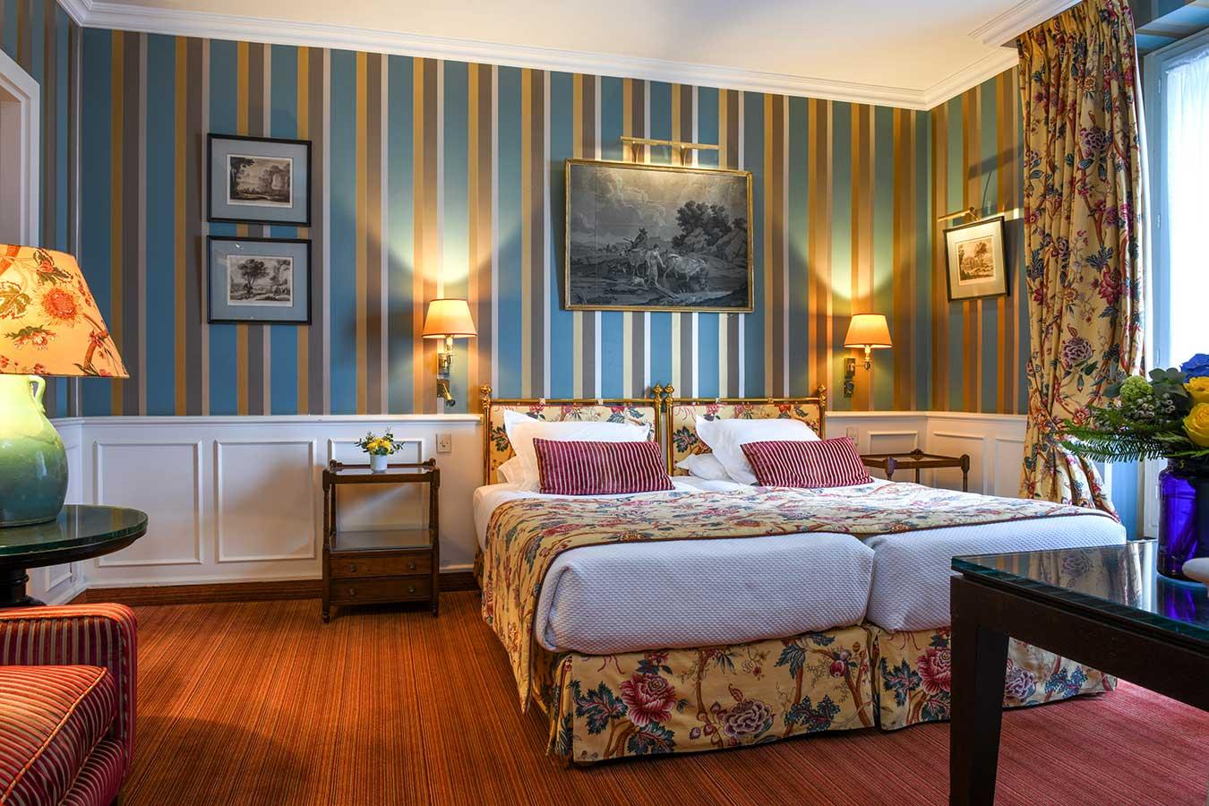 Parisienne Deluxe - Grand lit en configuration twin, harmonie de couleurs jaune, bleu et rose avec papier peint à rayures verticales