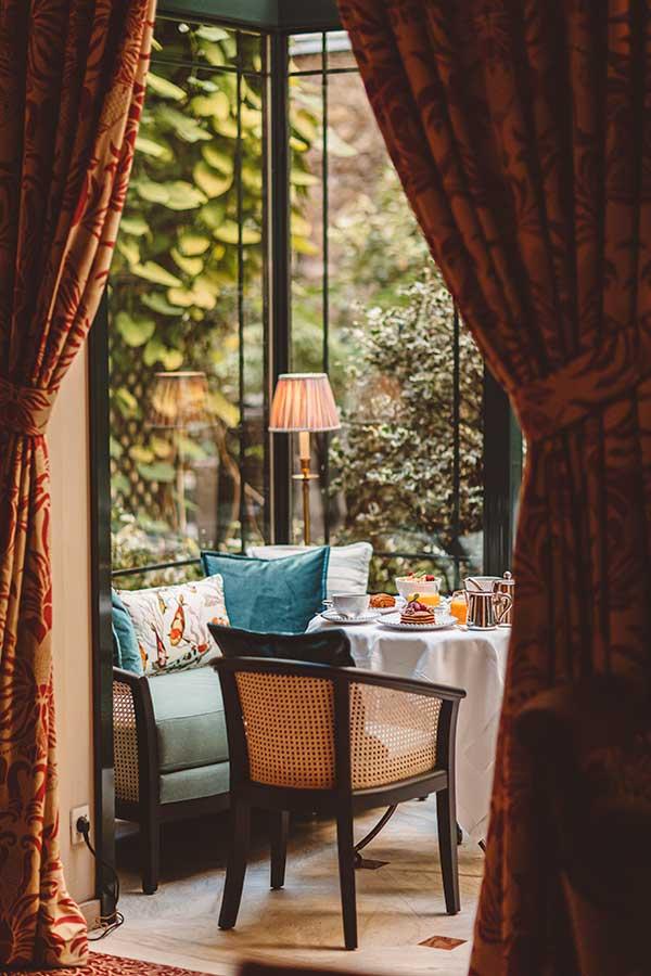 Petit-déjeuner - Table ronde avec nappe blanche, petit-déjeuner composé de boissons chaudes, pancakes, salade de fruits et viennoiseries, banquette verte et coussins à motif sous la verrière ensoleillée