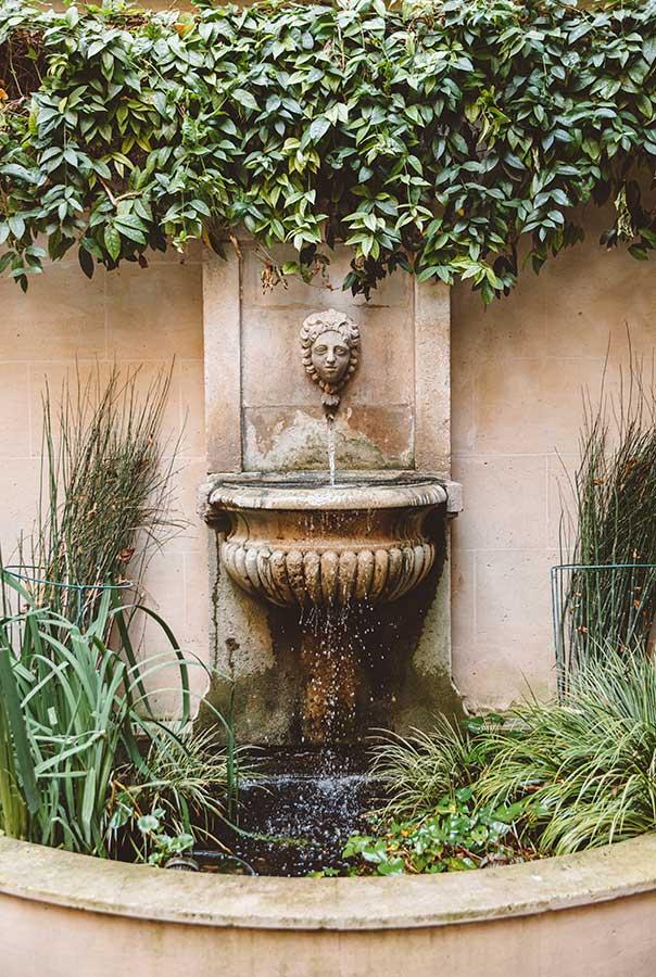 Jardin - Fontaine en pierre avec jet d'eau, végétation