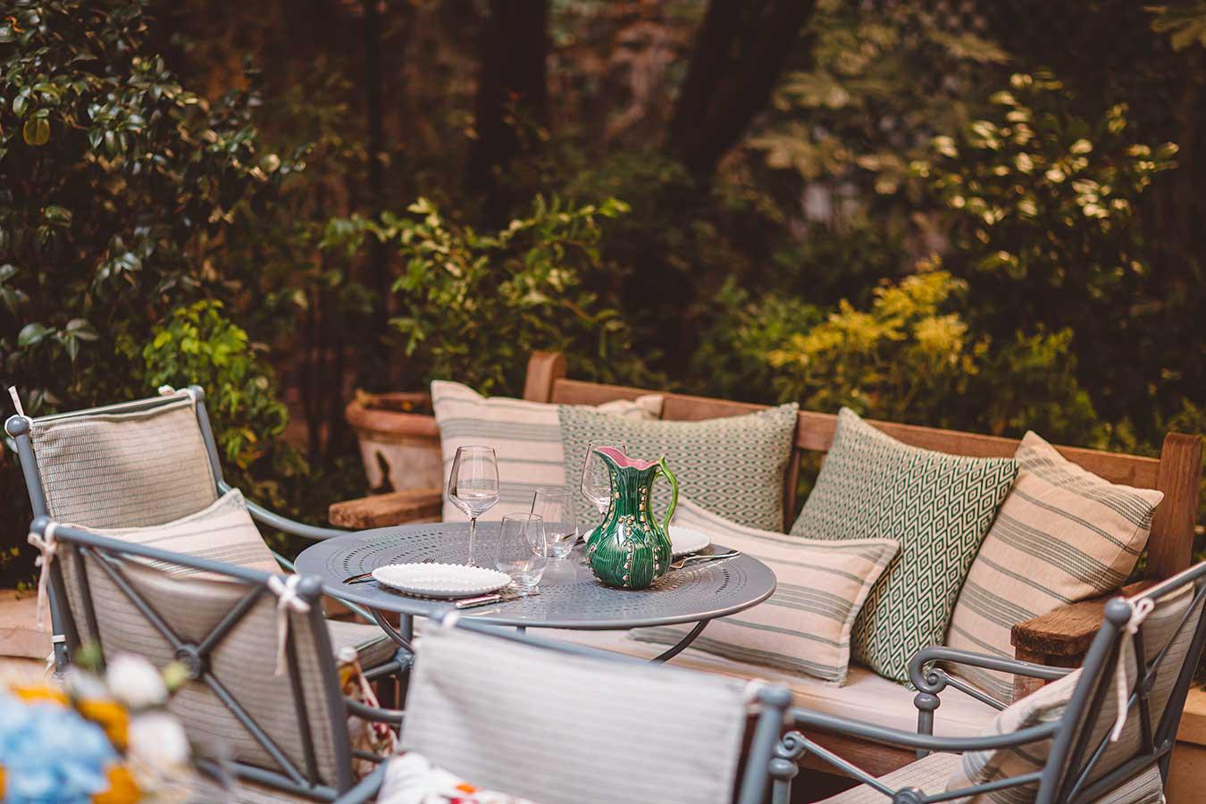 Jardin - Table de jardin dressée avec chaises et banquettes avec coussins dans les tons vert et beige