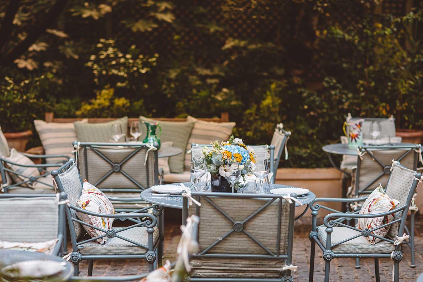 Jardin - Tables de jardin avec chaises et coussins colorés, bouquet de fleurs central dans les tons bleu et jaune