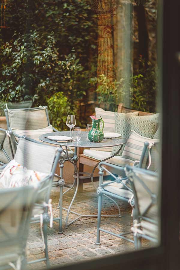 Jardin - Vue de la verrière, tables et chaises de jardin avec coussins fleuris, carafe verte