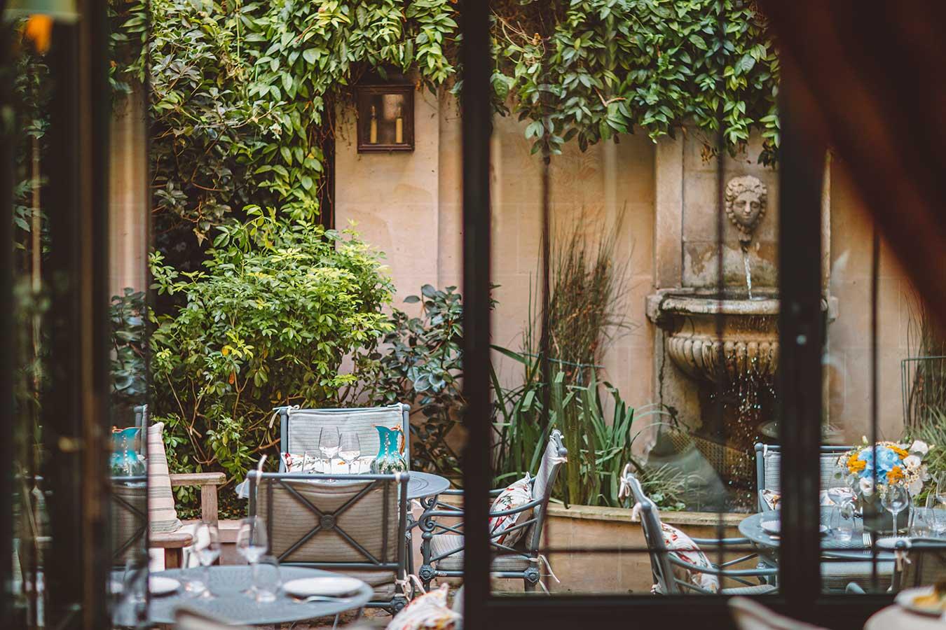 Jardin - Vue depuis la verrière sur le jardin avec tables, chaises, coussins colorés et fontaine