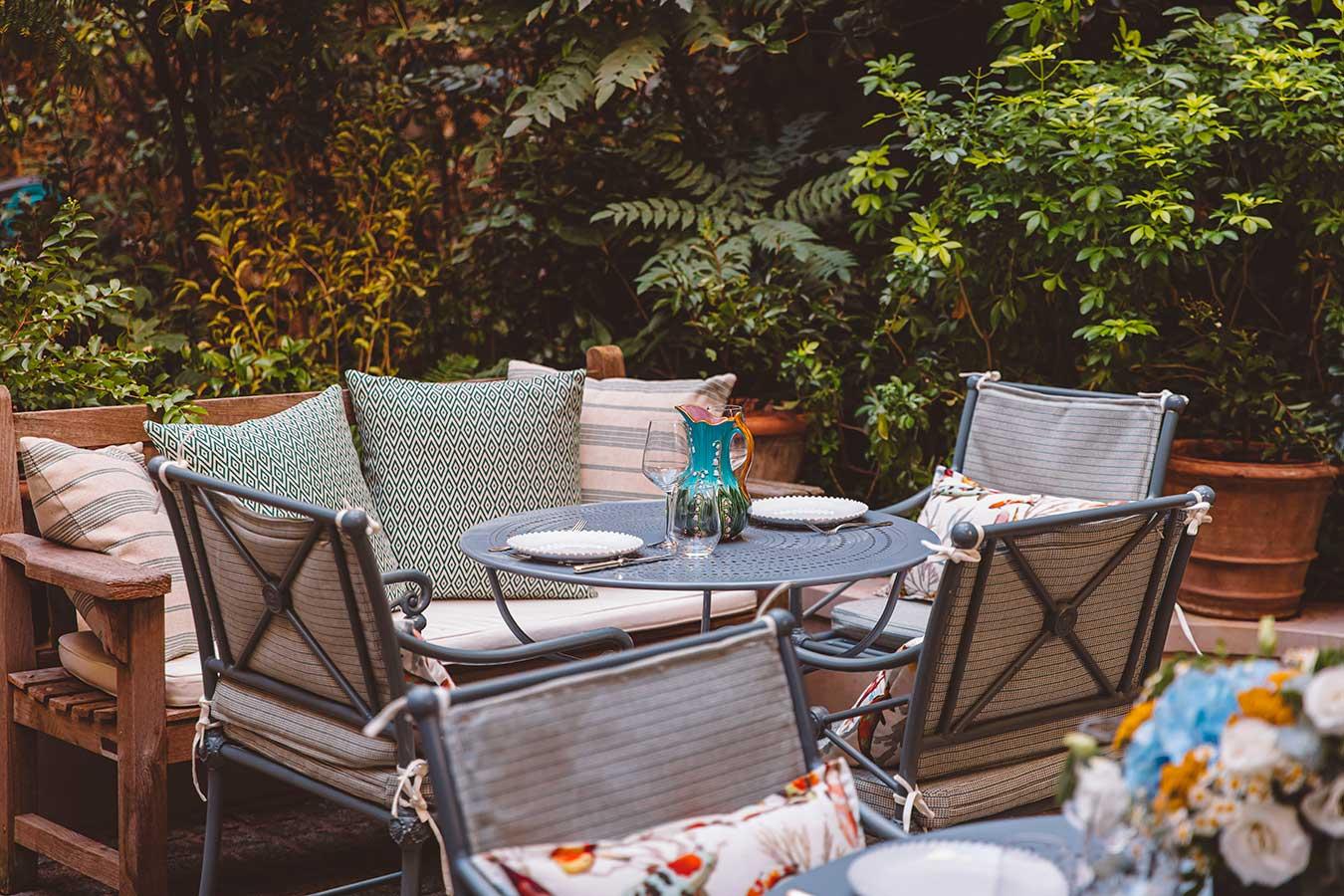 Jardin - Table de jardin dressée, chaises et banquettes avec coussins vert et beige