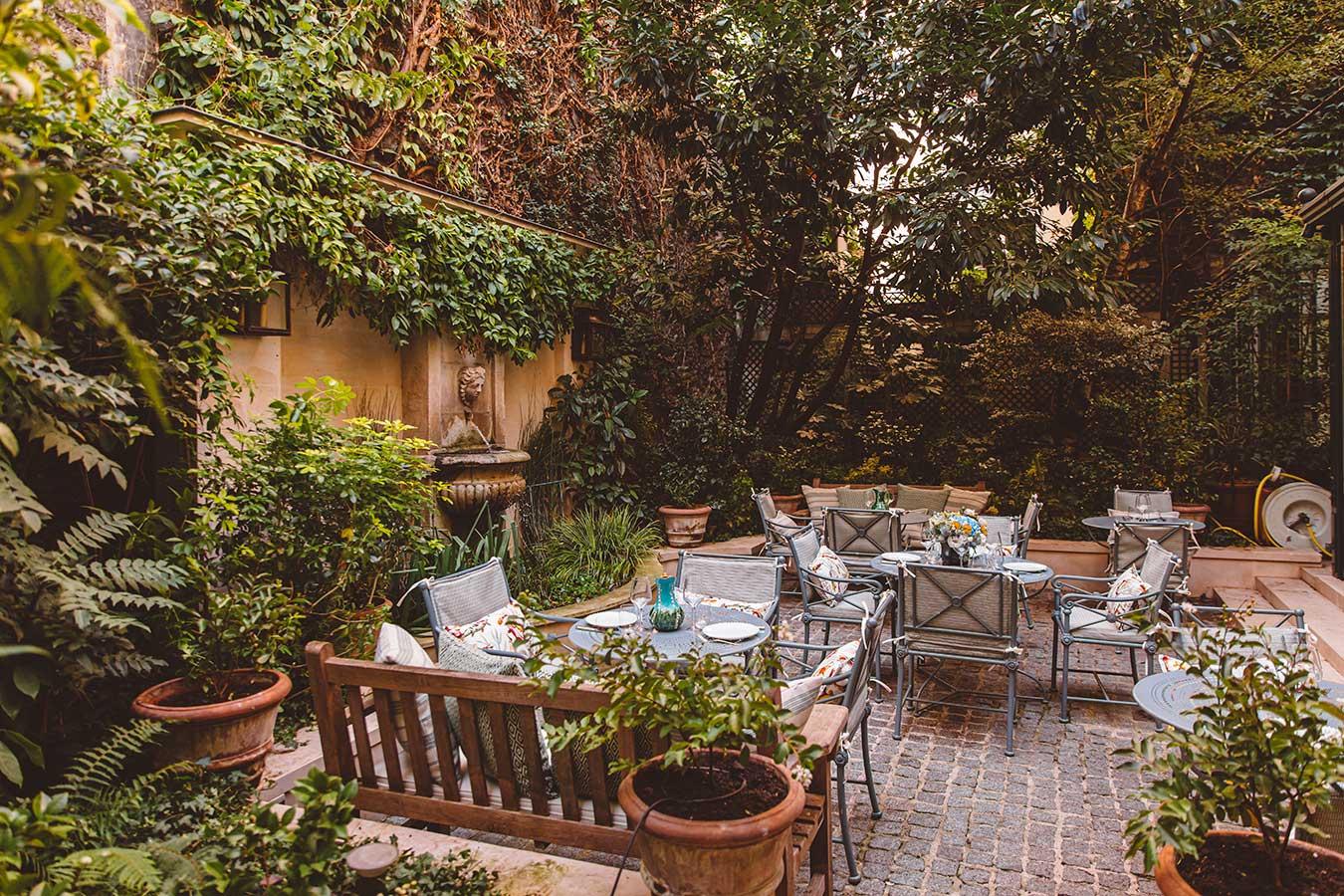 Jardin - Vue d'ensemble avec assises en bois, chaises et tables de jardin, fontaine et murs couverts de lierre grimpant