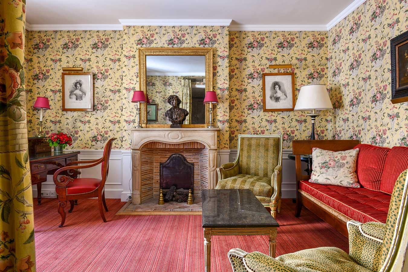 Appartement Terrasse - Salon avec table basse en marbre, bureau et fauteuil, cheminée, canapé rouge et fauteuil beige à motif léopard