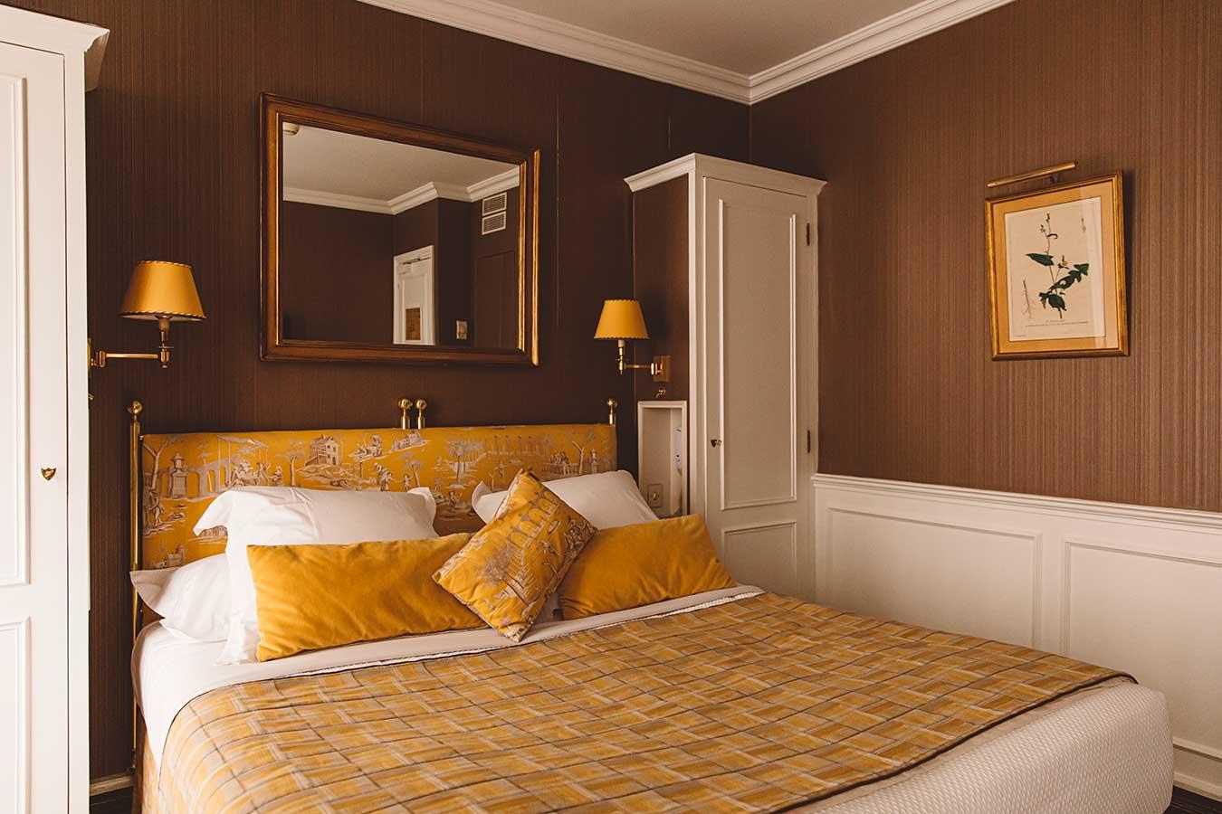 Parisienne - Chambre avec placard de chaque côté du lit, tissu jaune à motifs et papier peint marron