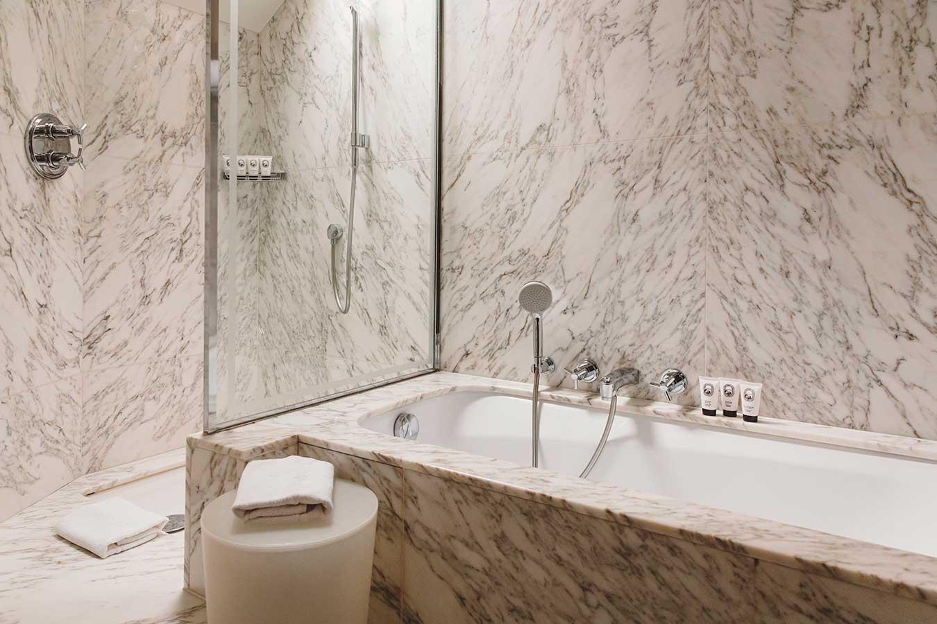 Salle de bain - Baignoire et douche en marbre, fenêtre, produits d'accueil Diptyque