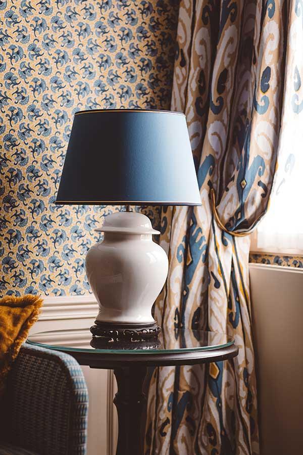 Appartement Terrasse - Grande lampe sur une table ronde, rideaux et canapés, dans une harmonie de bleu et jaune
