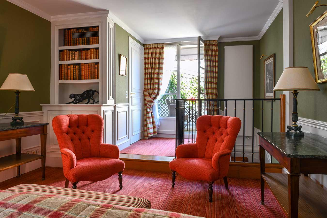 Appartement Terrasse - Chambre au 1er étage, fauteuils rouges côte à côté, bibliothèque avec statue panthère noire, balcon avec verdure