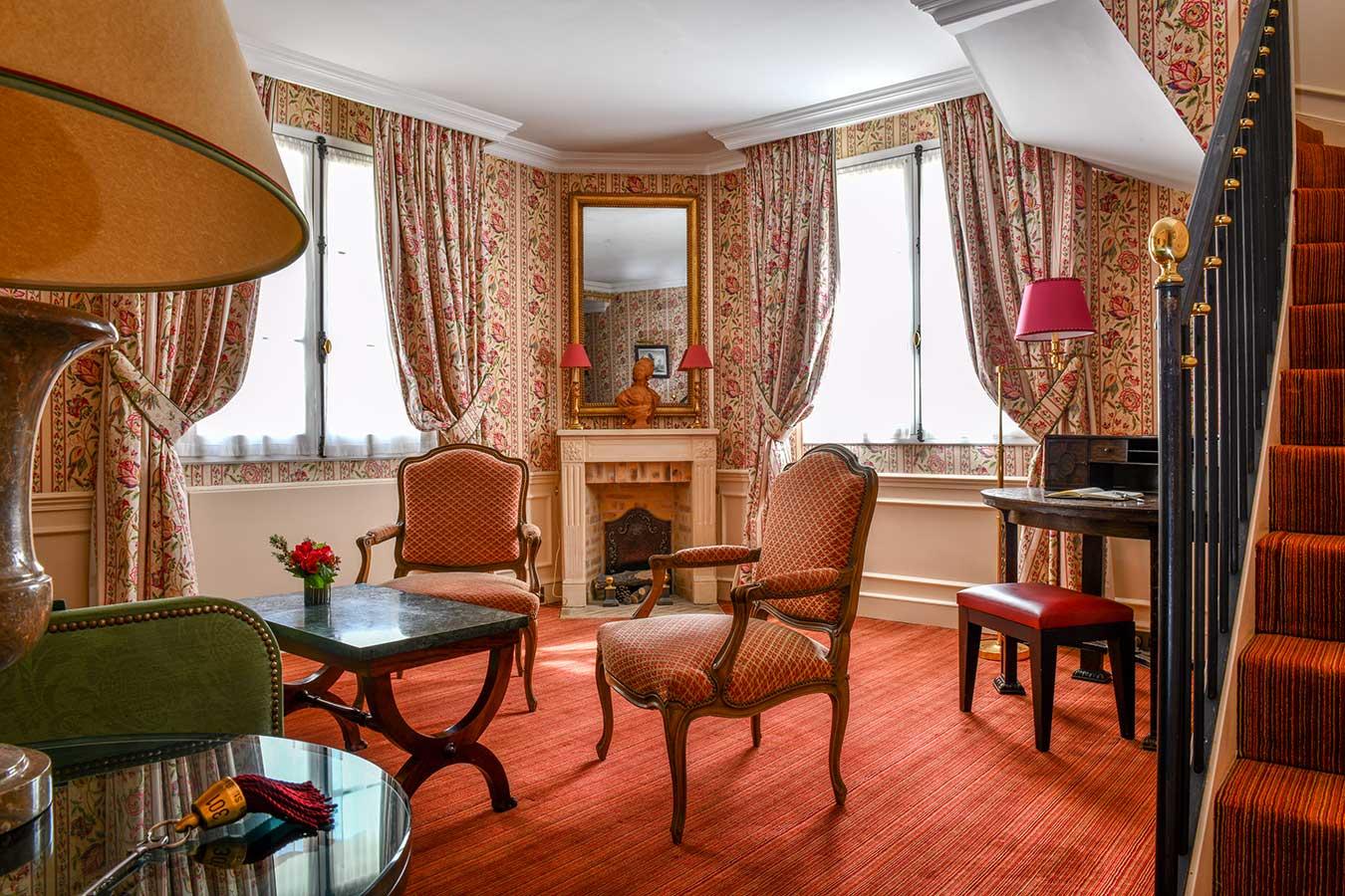 Appartement Terrasse - Grand salon avec escalier menant à la chambre, fauteuils, canapé, table basse, cheminée et bureau, dans une harmonie de rouge et rose