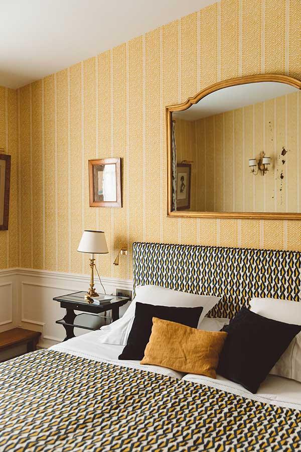 Appartement Terrasse - Grand lit, tête de lit, miroir or, table de chevet avec lampe, dans une harmonie bleu et jaune