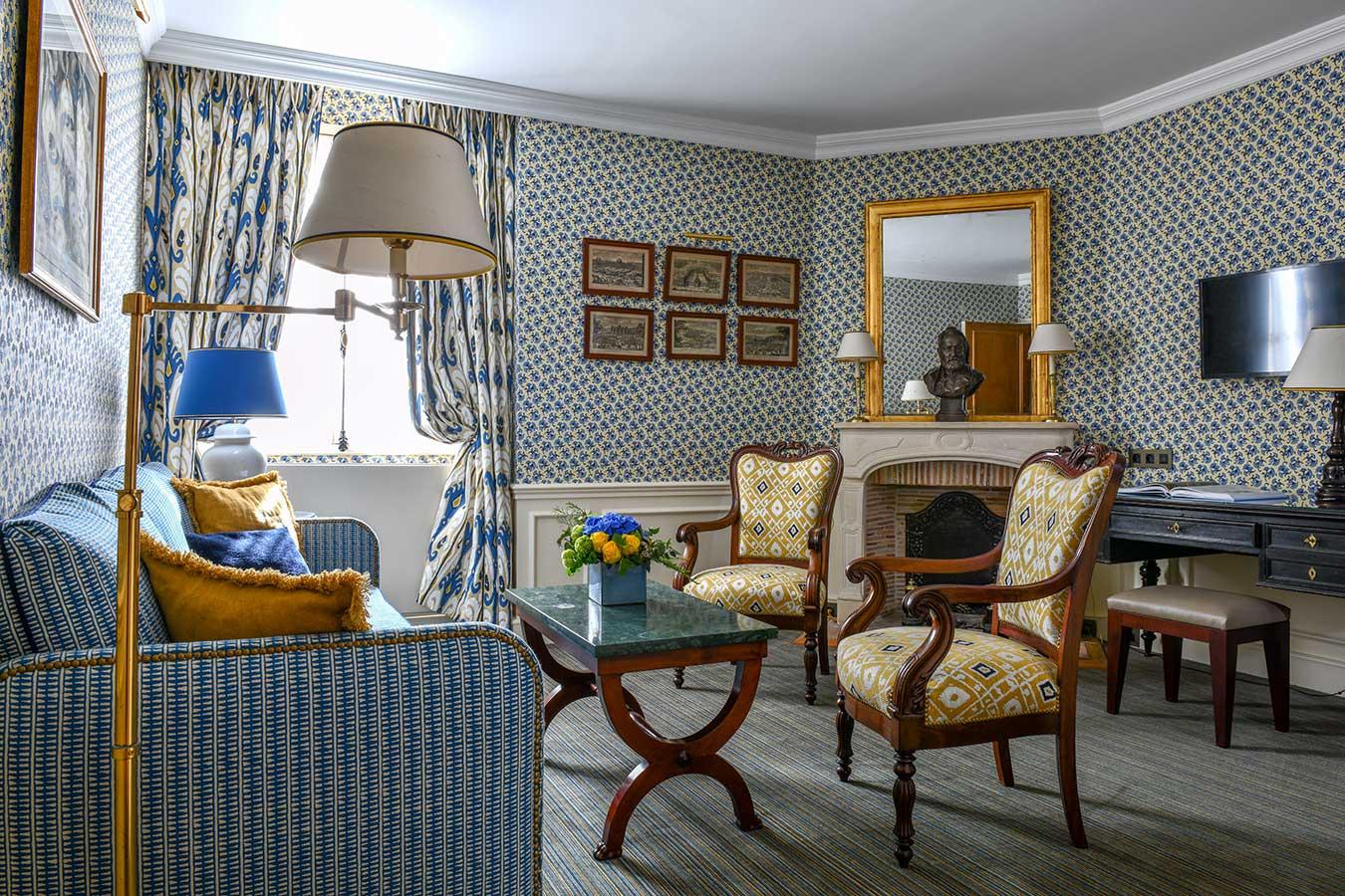 Appartement Terrasse - Grand salon avec canapé, fauteuils, table basse, bureau et cheminée, dans une harmonie de bleu et jaune