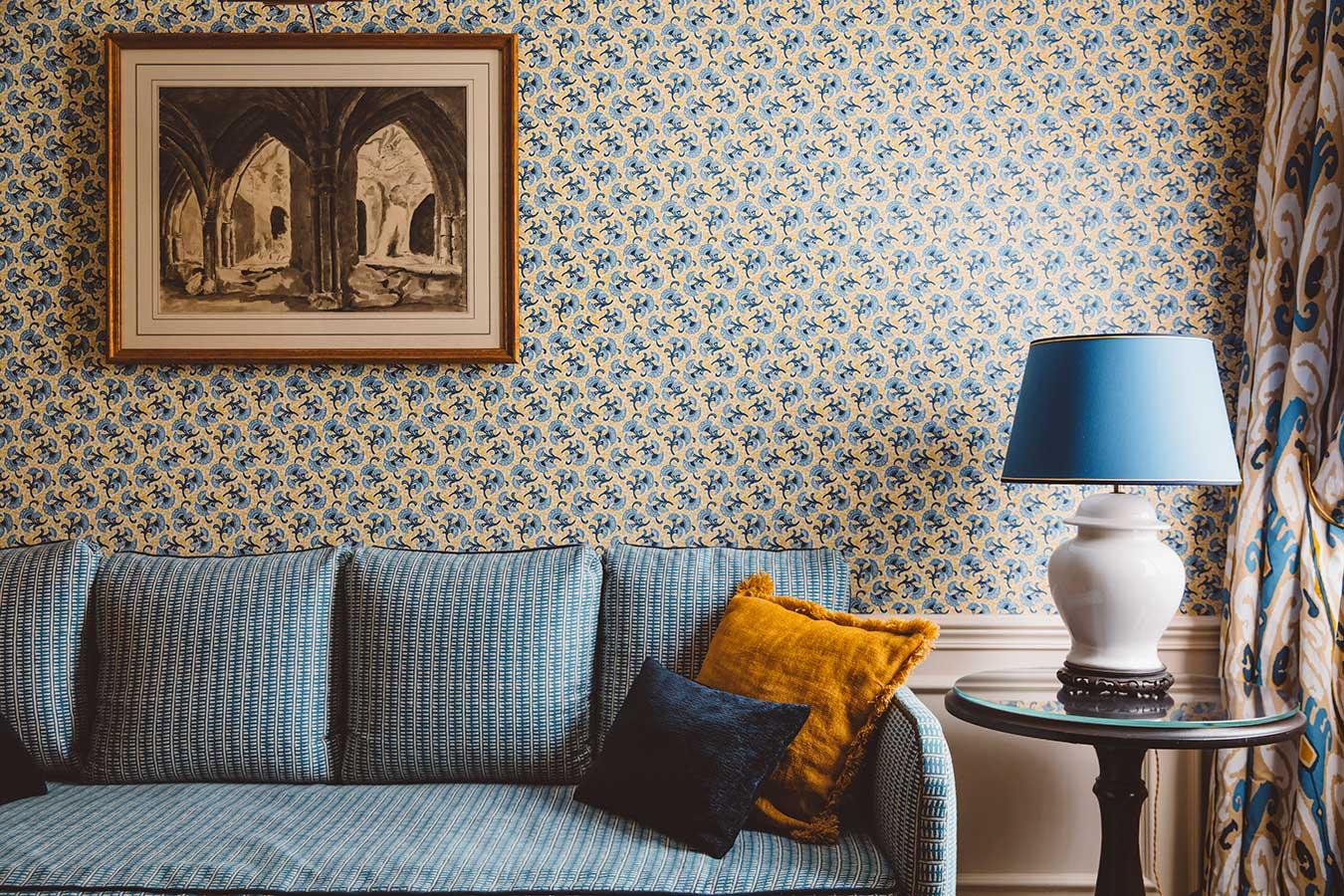 Appartement Terrasse - Grand canapé bleu, coussins, table et lampe, papier-peint fleuri dans une harmonie de bleu et jaune