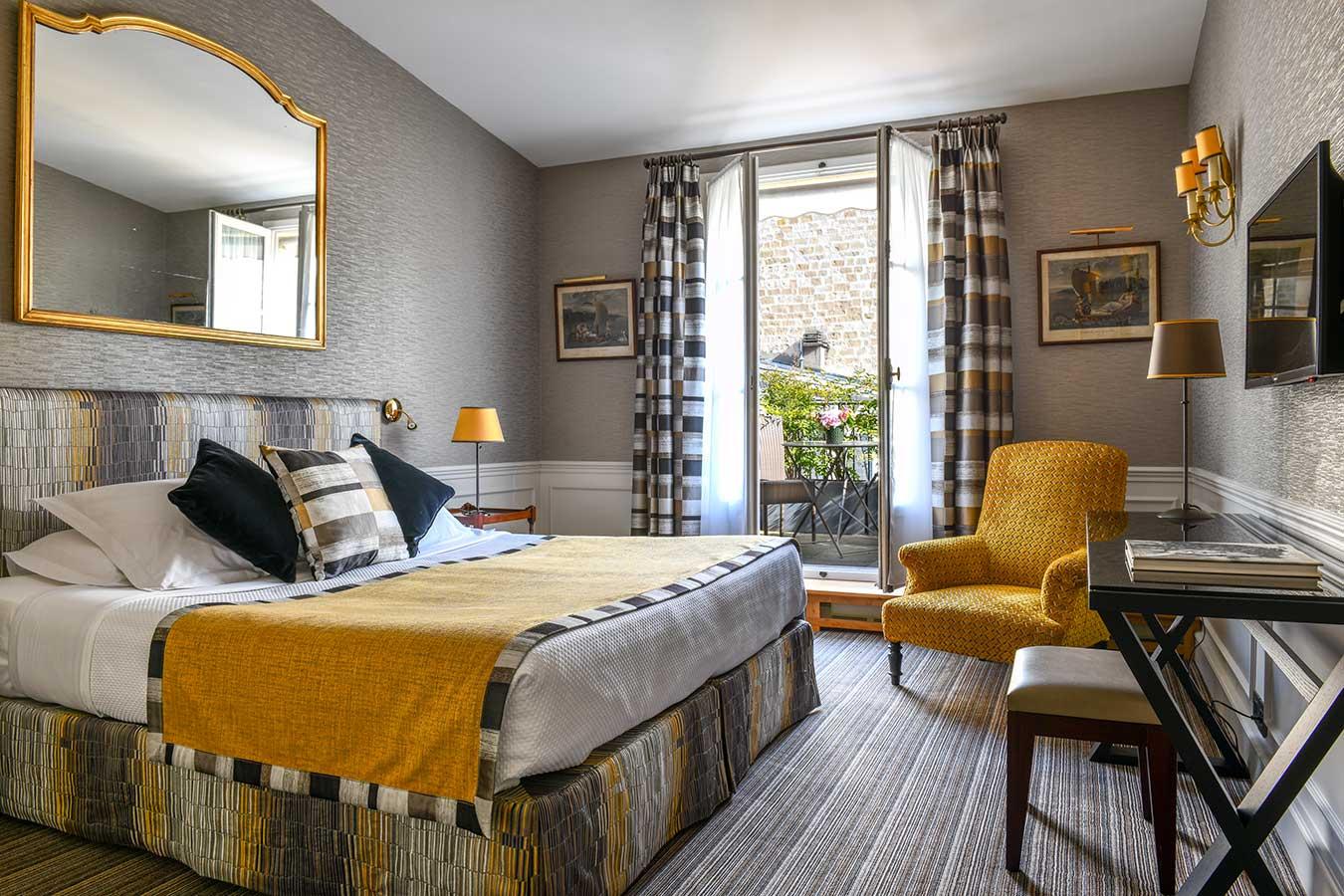 Appartement Terrasse - Grand lit avec miroir, fauteuil jaune, bureau, balcon donnant sur les toits de Paris, dans une harmonie de jaune, gris et noir