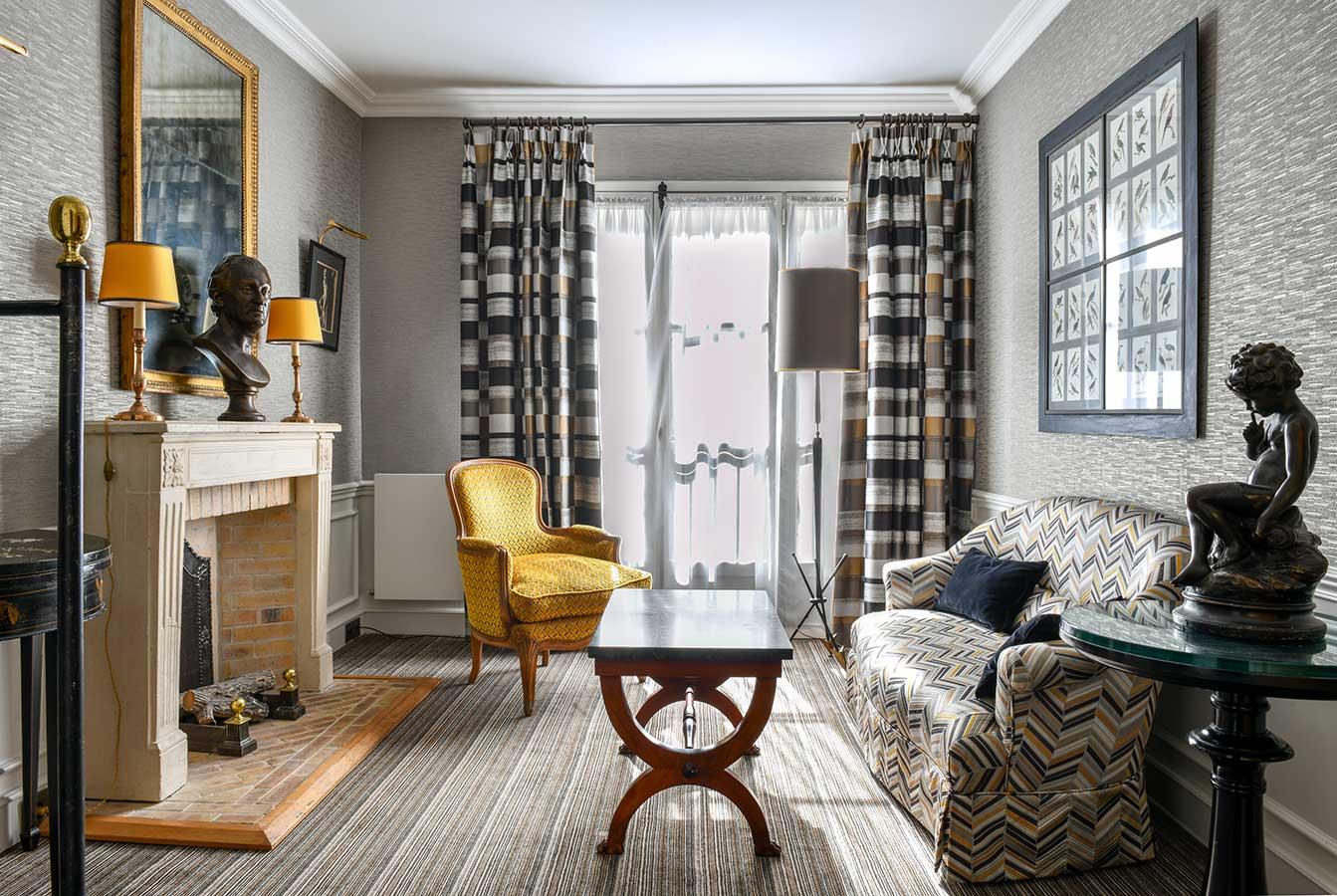 Appartement Terrasse - Grand salon avec cheminée, table basse en marbre, fauteuil jaune et canapé dans une harmonie de gris, jaune et noir