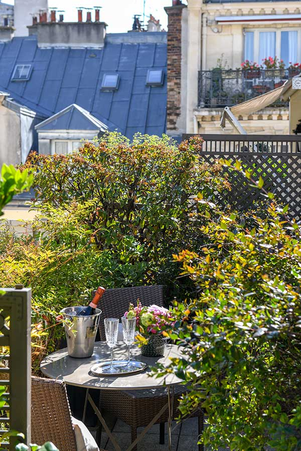 Appartement Terrasse - Terrasse donnant sur les toits de Paris, table ronde et chaises, sceau à champagne et bouquet de fleurs rose, végétation