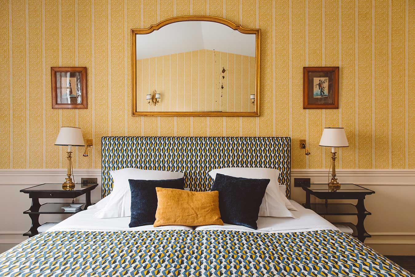 Appartement Terrasse - Grand lit, tables de chevet et lampes, grand miroir, dans une harmonie de bleu marine et jaune