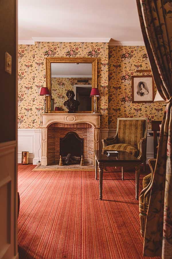 Appartement Terrasse - Vue de l'entrée, salon avec grande cheminée, miroir et fauteuil, dans une harmonie beige, rouge et jaune
